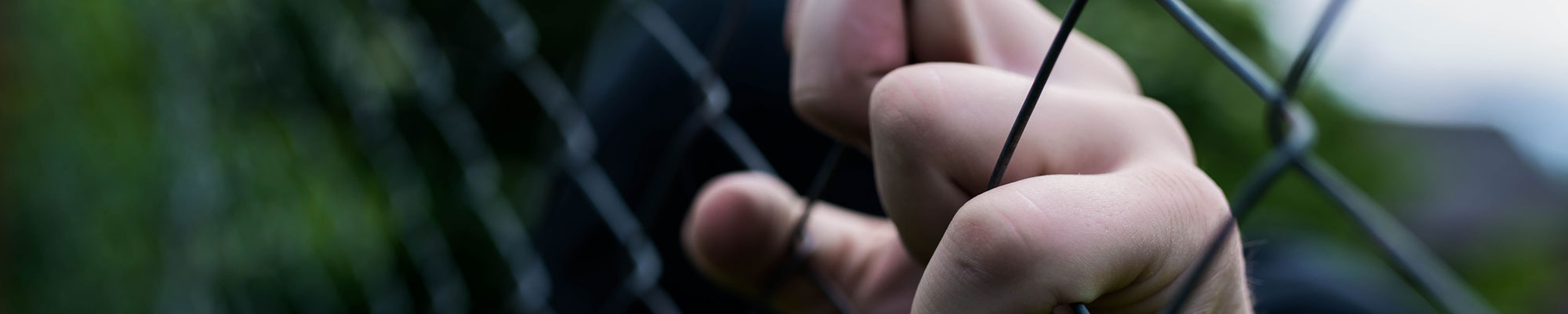 Person holding onto prison fence